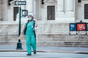 black physician in uniform crossing city road